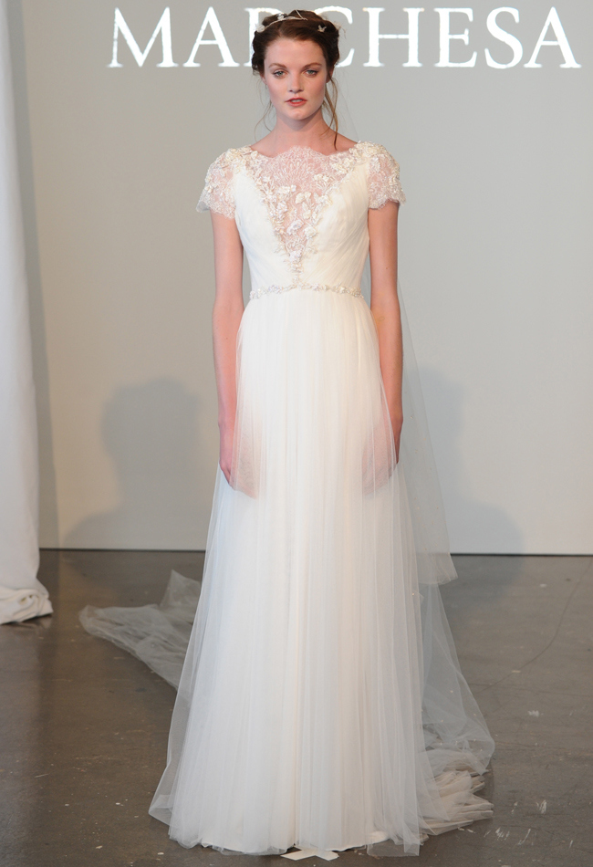 Grecian-inspired draped tulle A-line wedding dress with a high neckline, re-embroidered lace details, and short sleeves