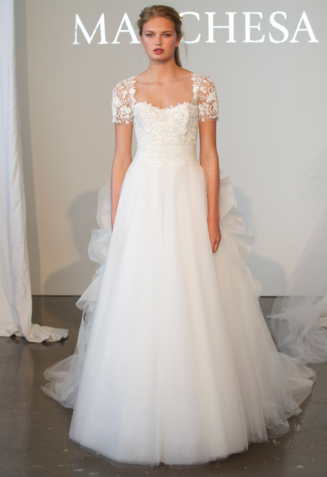 Tulle ball gown wedding dress with a fully embroidered bodice, short sleeves, and ruffled peplum